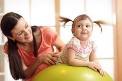 Mother and child playing with gymnastic ball at home. Mother and child daughter playing with gymnastic ball at home Royalty Free Stock Image