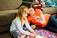 Mother and child daughter playing together, build from the constructor. cute her son play Stock Image