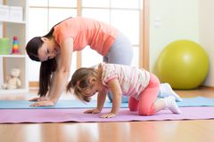 Mother and child daughter practicing yoga together at home. Sport and family concept