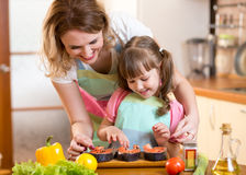 Mother with child daughter preparing fish in Royalty Free Stock Photography