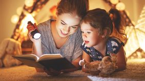 Mother and child daughter reading a book and a flashlight before. Reading and family games in   tent. mother and child daughter reading book and flashlight Royalty Free Stock Image