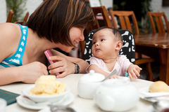 Mother and child at the dining table. With kissing expressions Royalty Free Stock Images