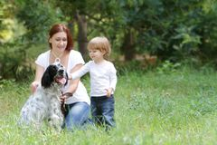 Mother and child with dog outdoors Royalty Free Stock Photography
