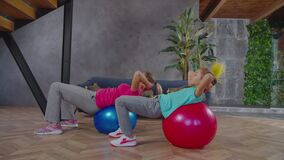 Mother and child doing crunches on stability ball