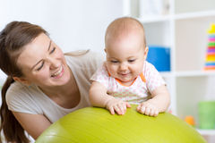 Mother with child doing exercises with green gymnastic ball at home. Concept of caring for the baby's health. Mother with happy child doing exercises with green Royalty Free Stock Photo