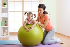 Mother with childdoing exercises with gymnastic ball at home. Concept of caring for the baby`s health. Mother with child doing exercises with green gymnastic royalty free stock image