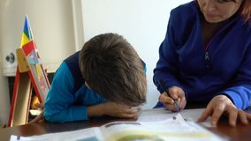 Mother and child doing school homework, camera rotating zoom out stock video