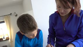 Mother and child doing school homework, tilt and zoom out. Hd video stock footage