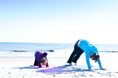 Mother and child doing yoga. Baby and mother doing yoga on the beach Stock Photography