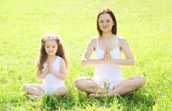 Mother and child doing yoga meditating in pose lotus. Mother and child doing yoga meditating on grass in pose lotus Royalty Free Stock Photography