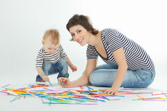 Mother and child are drawing. Against white background stock photos