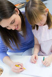 Mother and Child drawing with crayons, sitting at table in kitchen Royalty Free Stock Photography