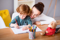 Mother and child drawing while sitting Stock Images