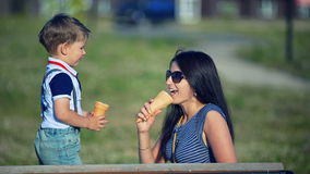 Mother and child eating ice cream outdoors in summer day stock footage