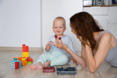 Mother and child eating together Stock Photos