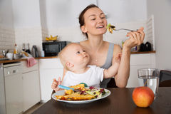 Mother and child eating together Stock Image