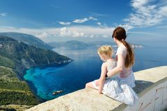 Mother and child enjoying the view of picturesque jagged coastline of Kefalonia with clear turquoise waters, surrounded by steep royalty free stock photo