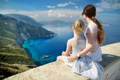 Mother and child enjoying the view of picturesque jagged coastline of Kefalonia with clear turquoise waters, surrounded by steep stock photo
