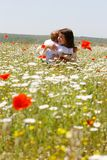 Mother and child in field. Mother and son in traditional clothes in flower field Stock Image