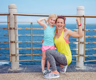 Mother and child in fitness outfit on embankment showing biceps Stock Images