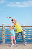 Mother and child in fitness outfit stretching on embankment Stock Photo