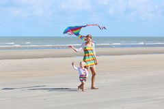 Mother and child flying kite on the beach Royalty Free Stock Photos