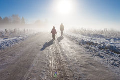 Mother and child on foggy snow farm road Stock Photo