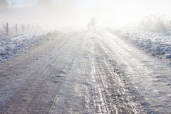 Mother and child on foggy snow farm road Stock Photography