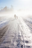 Mother and child on foggy snow road Royalty Free Stock Images