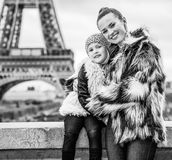 Mother and child in front of Eiffel tower in Paris embracing. The Party Season in Paris. Portrait of happy trendy mother and child in the front of Eiffel tower Royalty Free Stock Photos