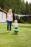 Mother and child in garden. Full length of adorable child pushing a wheelbarrow in garden while walking with mother Royalty Free Stock Photo