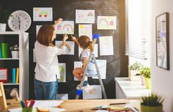 Mother and child girl hang their drawings on wall Royalty Free Stock Photo