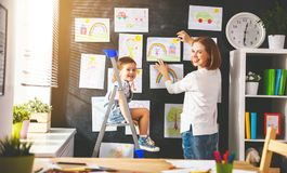 Mother and child girl hang their drawings on wall Royalty Free Stock Photography