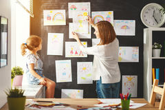 Mother and child girl hang their drawings on wall Stock Photo