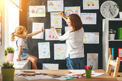 Mother and child girl hang their drawings on wall Royalty Free Stock Images