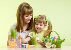 Mother and child girl paint easter eggs. Over green background Stock Image