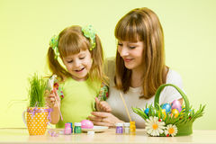 Mother and child girl paint eggs preparing to Easter holiday Royalty Free Stock Image