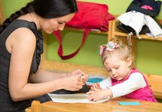 Mother and child girl playing in kindergarten in Montessori preschool Royalty Free Stock Photography
