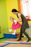 Mother and child girl playing in kindergarten in Montessori preschool Stock Image