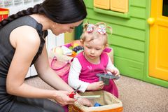 Mother and child girl playing in kindergarten in Montessori preschool. Class royalty free stock image