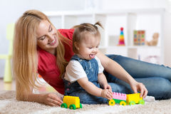 Mother and child girl playing together indoor Stock Photography