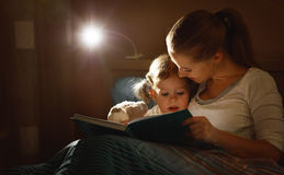 Mother and child girl reading a book in bed. Before going to sleep Stock Photos