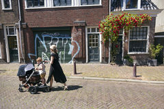 Mother and child girl walk the street with carriage in leeuwarde. Leeuwarden, Netherlands, 11 june 2017: mother and child girl with carriage pass house with Royalty Free Stock Photography