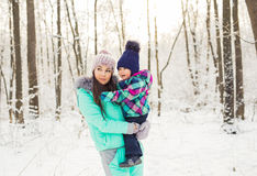 Mother and child girl on a winter walk in nature. Happy family.  Stock Photos