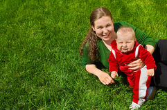 Mother and child on grass. Young mother and her little baby are on green grass. They are smiling. There is free area near them from grass. Green background. Red Royalty Free Stock Image