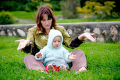 Mother and child on grass. Mother and her baby sitting on the grass and playing stock images