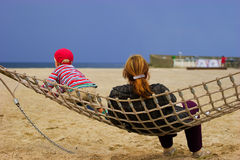 Mother and child in hammock. Resting at sandy beach Royalty Free Stock Image