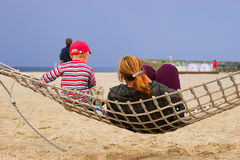 Mother and child in hammock. Resting at sandy beach Royalty Free Stock Photo
