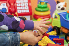 Mother and child hand on a colored toys background Royalty Free Stock Photo