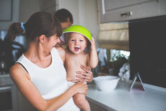Mother with a child on hands. Mother in the kitchen holding the baby in her arms. The effect of film photography Stock Photo